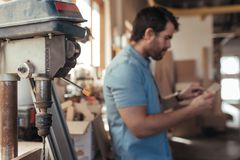 Woodworker using a tablet at his workbench full of tools. Closeup of a drill press in a carpentry workshop with a young carpenter working on a digital tablet at Royalty Free Stock Photography