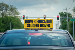 Closeup of drivers ed car at stoplight. High school student driver sign on top of car outside in traffic stock images