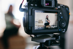 Closeup of a DSLR camera recording a video blog. Young female vlogger recording content for her vlog sitting in her living room. Closeup of camera screen Stock Photos