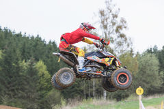 Closeup dynamic shot of quad rider in high jumping Stock Photography