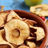 Slices of dried apple served as appetizer or snack. Closeup of an earthenware bowl with some slices of dried apple, served as appetizer or snack, on a blue royalty free stock image