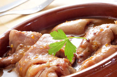 Manitas de cerdo, stewed pig feet typical of Spain. Closeup of a earthenware casserole with manitas de cerdo, stewed pig feet typical of Spain Royalty Free Stock Photography