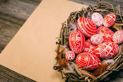 Closeup Easter eggs with pattern inside bird nest on right side of vintage sheet of paper on wood board. Top view royalty free stock image