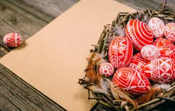 Closeup Easter eggs with pattern inside nest on right side of vintage sheet of paper on wood board stock images