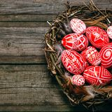 Closeup Easter red eggs with folk white pattern inside bird nest on rustic wood board. Top view stock photo