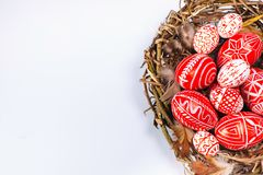 Closeup Easter red eggs with folk white pattern inside bird nest on white. Top view stock photo