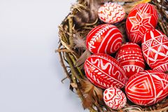Closeup Easter red eggs with folk white pattern inside bird nest on white background. Top view. Ukrainian traditional eggs royalty free stock image