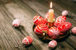 Closeup Easter red eggs with folk white pattern lay around on brass candlestick with burning candle and scattered eggs on rustic t Stock Photos