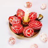 Closeup Easter red eggs with folk white pattern lay around brass candlestick which stand on white background and eggs scattered ar. Ound. Ukrainian traditional royalty free stock image