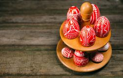 Closeup Easter red eggs with folk white pattern lay around stand for eggs which stand on rustic wood background. Top view. Ukrainian traditional eggs pisanka stock photos