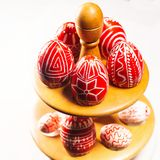Closeup Easter red eggs with folk white pattern lay around on stand for eggs which stand on white background. Ukrainian traditiona. L eggs pisanka and krashanka royalty free stock photography