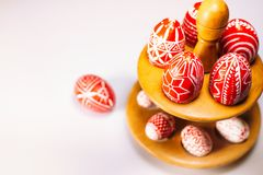 Closeup Easter red eggs with folk white pattern lay around on stand for eggs which stand on white background. Ukrainian traditiona. L eggs pisanka and krashanka stock photos