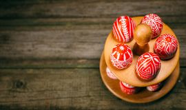 Closeup Easter red eggs with folk white pattern lay around stand for eggs which stand on rustic wood background. Top view. Ukraini. An traditional eggs pisanka royalty free stock photos