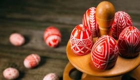 Closeup Easter red eggs with folk white pattern lay on stand for eggs which stand on rustic wood background and eggs scattered. Uk. Rainian traditional eggs royalty free stock photography
