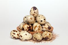 Closeup Easter small fresh textural quail eggs in round wooden bowl with textile on white background. Concept traditional stock images