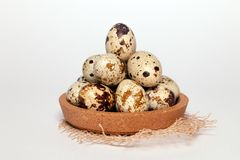 Closeup Easter small fresh textural quail eggs in round wooden bowl with textile on white background. Concept traditional royalty free stock photography