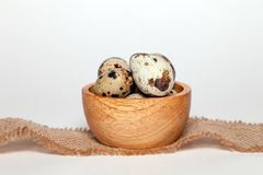 Closeup Easter small fresh textural quail eggs in round wooden bowl with textile on white background. Concept traditional royalty free stock images