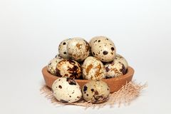 Closeup Easter small fresh textural quail eggs in round wooden bowl with textile on white background. Concept traditional stock photos