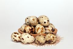 Closeup Easter small fresh textural quail eggs in round wooden bowl with textile on white background. Concept traditional stock photography