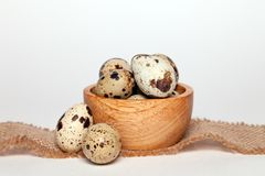 Closeup Easter small fresh textural quail eggs in round wooden bowl with textile on white background. Concept traditional stock image