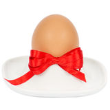 Closeup of an egg and a porcelain egg cup Royalty Free Stock Photos
