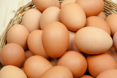 Closeup of eggs put in a wicker basket in wooden background. Closeup of Eggs decorated in a wicker basket in wooden background from top view Royalty Free Stock Photos