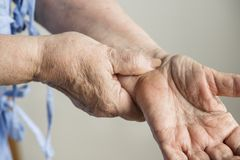 Closeup of elderly hands checking pulse stock photo