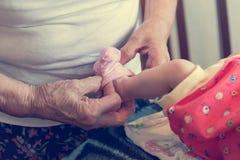 Closeup of elderly hands putting socks on newborn feet. Grandmother dressing up her granddaughter Royalty Free Stock Image