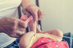 Closeup of elderly hands putting socks on newborn feet. Grandmother dressing up her granddaughter stock photos