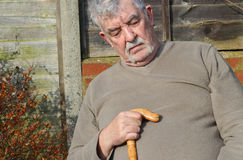 Closeup of an elderly man asleep. A closeup of an elderly man with a walking stick asleep outside. The man is tired and relaxing in the sunshine royalty free stock photos