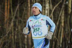Closeup elderly man runner running on track in winter forest Royalty Free Stock Photography