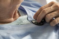 Closeup of elderly woman checking heart beats with stethoscope royalty free stock images