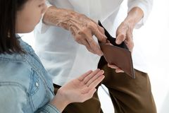 Closeup elderly woman hands open wallet,grandmother or guardian giving pocket money to granddaughter,asian little girl demanding royalty free stock photo