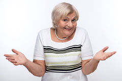 Closeup of elderly woman shrugging shoulders. Having no clue. Cropped image of elderly woman shrugging her shoulders with clueless expression while standing Stock Image