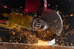 Closeup on electric saw and hands of worker with sparks. Stock Image