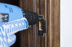 Closeup of electric skrewdriver,male hand in gloves using it for repairing a part of door handle,lock stock images