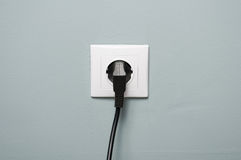Closeup of electric socket with black cable plugged in Stock Images