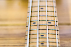 Closeup of electrical bass guitar fingerboard. Defocused, deep of field, wooden background Stock Image