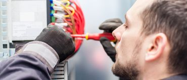 Closeup of electrician engineer works with electric cable wires stock image
