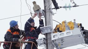Electrician unfixes fasteners on metal structure on winter day. Closeup electrician in helmet unfixes fasteners on metal structure holding equipment on tower on stock video footage