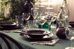 Closeup of elegant dining table with green tablecloth, black plates and wine glasses. Concept stock photography