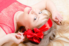 Closeup on elegant romantic blond young woman with blue eyes pinup girl with red headwrap lying in bed & looking at camera. Elegant romantic blond young woman Stock Photography