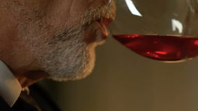 Closeup of elegant senior man drinking red wine in restaurant, romantic date stock footage