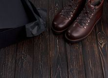 Closeup of elegant stylish brown male boots with shoes box on wooden background. Top view of shoes. Horizontal photo Stock Photo