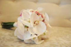 Closeup of an elegant wedding bouquet with large white orchids and roses. A floral bridal arrangement rested on a silky cushion ready for the bride-to-be stock photos