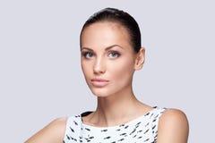 Closeup on elegant woman in fashionable stylish white dress posing in studio. Royalty Free Stock Photography