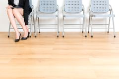 Closeup of elegant young office worker lady. Wearing high heel shoes long time feeling ankle pain uncomfortable and sitting on wood floor seat chair waiting for Stock Image