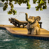 Closeup elephant statue spraying water in a swimming pool next to the sea , Thailand Stock Image