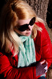 Closeup emotions of a caucasian woman with red jacket and sunglasses Stock Photography