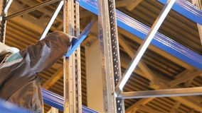 Closeup Employee Mounts Storage Shelf Fixing Part in Warehouse stock video footage